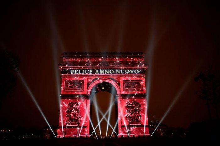 """2016年12月31日夜,在法国巴黎,""""新年快乐""""字样的图案被映在该市标志性建筑凯旋门上。 为迎接新年,这里举行了一场灯光秀。"""
