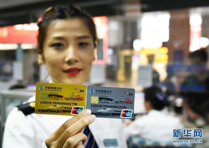 5月1日,天津站售票人员展示准备发售的京津城际优惠卡(左为金卡,右为银卡)。